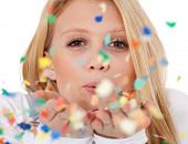 Attractive teenage girl having fun with confetti. All on white background.