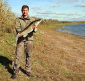 fishing man on coast with big zander fish