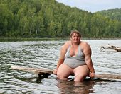 stock photo of flabby  - overweight woman sitting on stage in lake - JPG
