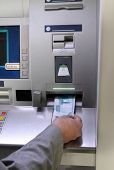 man's hand inserting banknote into cash dispense