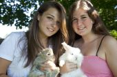 Two teenage girls holding baby rabbits