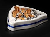White ceramic ash tray full of cigarette butts on black background