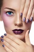 Close-up portrait of young beautiful woman with stylish make-up and glitter manicure