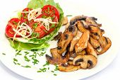 Plate with tomato salad and fried turkey hen strips with button mushrooms on white background