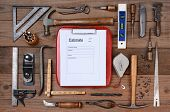 High angle shot of a contractors estimate form surrounded by his well used tools. Horizontal format