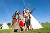 stock photo of wigwams  - Three North American Indians stand near a wigwam - JPG