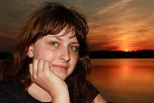 image of 13 year old  - One teen girl 13 years old caucasian closeup portrait with freckles resting hand on chin against a background of forest lake in the spring in the evening at sunset - JPG