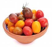 an earthenware bowl with baby plum tomatoes of different colors on a white background