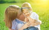 pic of tickling  - happy family on nature outdoors mother tickle baby daughter and laugh on the green meadow