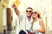 summer holidays, dating, city break and tourism concept - couple with camera and travellers guide