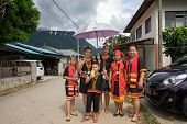 SARAWAK, MALAYSIA: JUNE 1, 2014: A family wearing traditional Bidayuh costumes wait for the parade t