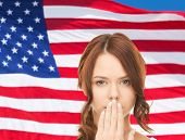 usa politics, conspiracy and secrecy concept - woman with hand over mouth on american flag background