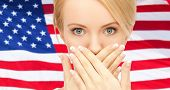 usa politics, conspiracy and secrecy concept - woman with hands over mouth on american flag backgrou