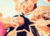 summer, holidays, vacation, happy people concept - group of girls looking down and showing finger fi