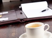 Old Fashioned Leather Folder With Blank Paper And A Cup Of Coffee