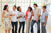 Coworkers laugh and celebrate accomplishment and enjoy party in the office