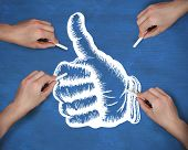 Composite image of multiple hands drawing thumbs up with chalk against navy blue