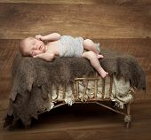 pretty little newborn girl sleeping on a cot. retro style