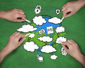 Composite image of multiple hands drawing clouds with chalk against green