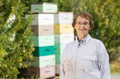 Portrait of confident female beekeeper standing at apiary