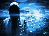 stock photo of incognito  - Hacker in a hood on dark blue digital background - JPG