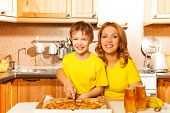 Happy Son And Mother Slicing Pizza In The Kitchen