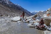 foto of gang  - GANGOTRI VALLEY - MAY 25: Two Hindu Sadhus take a holy dip in the freezing waters of the Ganges river at its source on May 25th, 2013 in the Gangotri Valley, India.