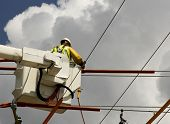stock photo of lineman  - lineman in a bucket hooking up high voltage wires - JPG