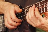 Hands of artist playing the bass guitar close up