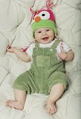 Portrait of cute happy 5 month old baby boy with funny hat. Photo of funny babe.