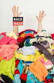 Man hands with the sale sign reaching out from a big pile of clothes and accessories.