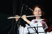 woman playing the flute celtic medieval music in traditional scottish clothes