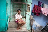 Indian Boy Sitting Near Colorful Wall Of His House