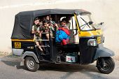 Indian school children at moto rickshaw