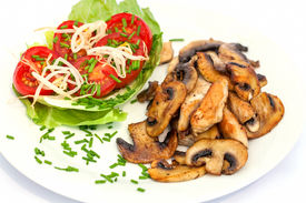 stock photo of turkey-hen  -  Plate with tomato salad and fried turkey hen strips with button mushrooms on white background  - JPG