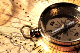 stock photo of treasure map  - Brass Compass on a Map - JPG