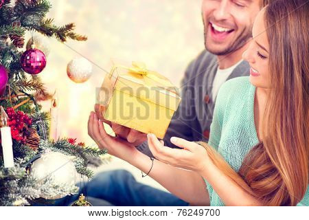Christmas Gift. Happy Couple with Christmas and New Year Gift at Home. Smiling Family Together. Chri