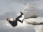 Young businessman scaling a rock   Business concept
