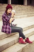 Brunette woman in hipster outfit sitting on steps and photographing on retro camera on the street. T