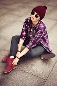Brunette woman in hipster outfit sitting on a scateboard on the street. Toned image