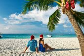 Couple in blue clothes on a tropical beach at Christmas.