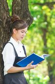 Student Reading Book In Park, Standing Under A Tree. Relaxing Outdoors Reading.