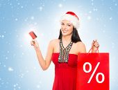Christmas shopper woman with a credit card over winter background