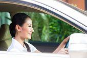 Asian woman driving new car