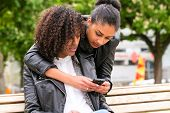 Two north African teen friends reading and writing text message on mobile phone in park