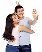 Happy laughing young couple joking and taking photo of themselves with smartphone on isolated white background