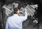 Man drawing a world map on a blackboard