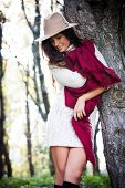 smiling young woman wearing hat,  red wool scarf and wool dress enjoy in autumn  day outdoor shot in wood