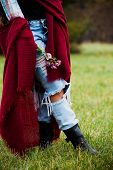 red wool scarf, flowers in hand,  blue torn jeans and leather boots, fashion autumn details outdoor shot in park