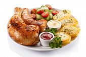 Barbecued chicken legs with baked potatoes and vegetables